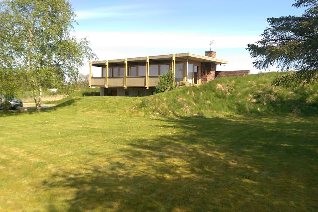 Huset er bygget på en skråning, med udsigt over vandet.