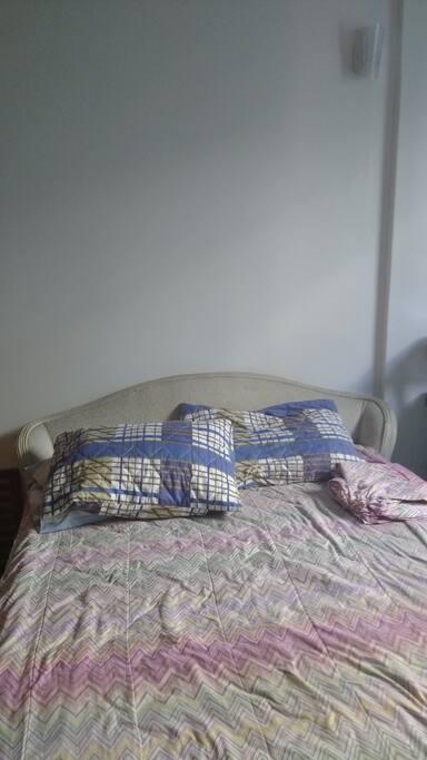 Big comfortable bed, bedroom has an wooden armchair.