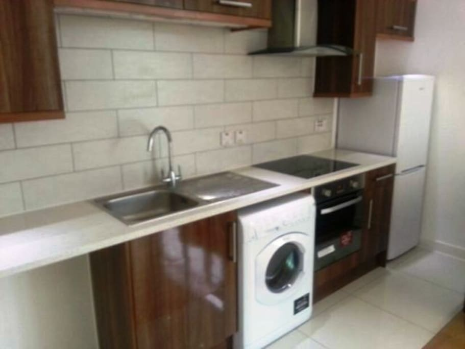 Kitchen unit provided with electric cooker, washing machine and fridge freezer.