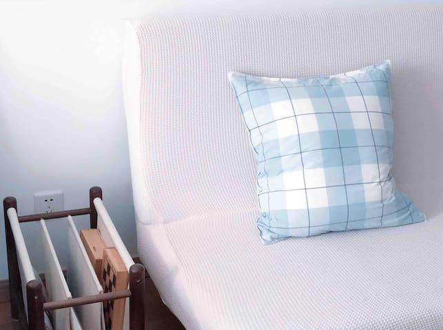 床头与沙发之间的 黑胡桃书本收纳架 沙发上的MUJI枕套
