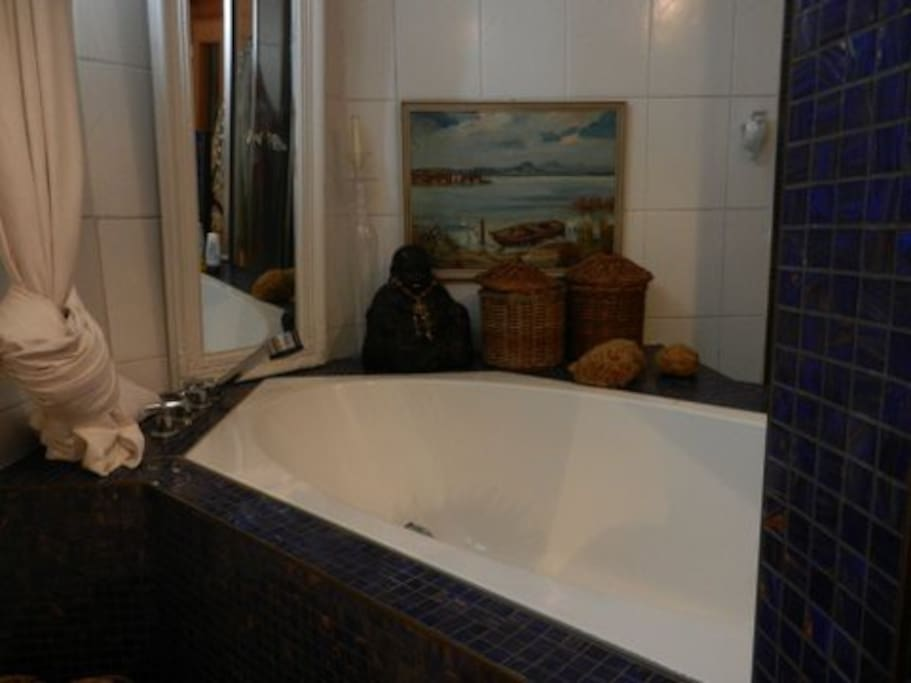 seperate bathroom with bathtub and two windows