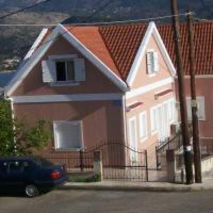 Το κατάλυμα, η πλάγια είσοδος,  η βεράντα - μπαλκόνι, ο κήπος και ο χώρος στάθμευσης. Θέα στο δρόμο, στην πόλη, στο βουνό και στη Λιμνοθάλασσα του Κούταβου