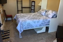 Bedroom with hanger rack and suitcase holder