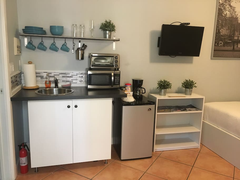 Kitchen with Microwave, refrigerator, coffee maker, glasses,plates and  utensils.