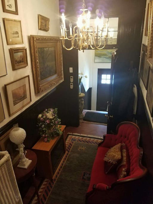 Lovely entranceway into the building filled with artwork, oriental rugs and antique furniture.