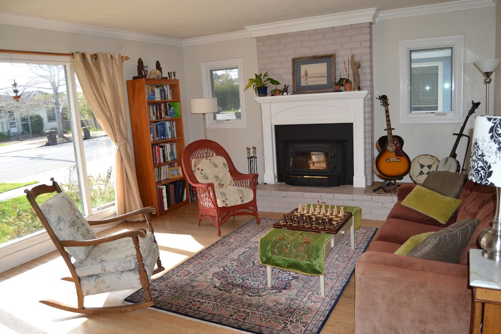 Living room has wood burning fire place and lots of natural light.