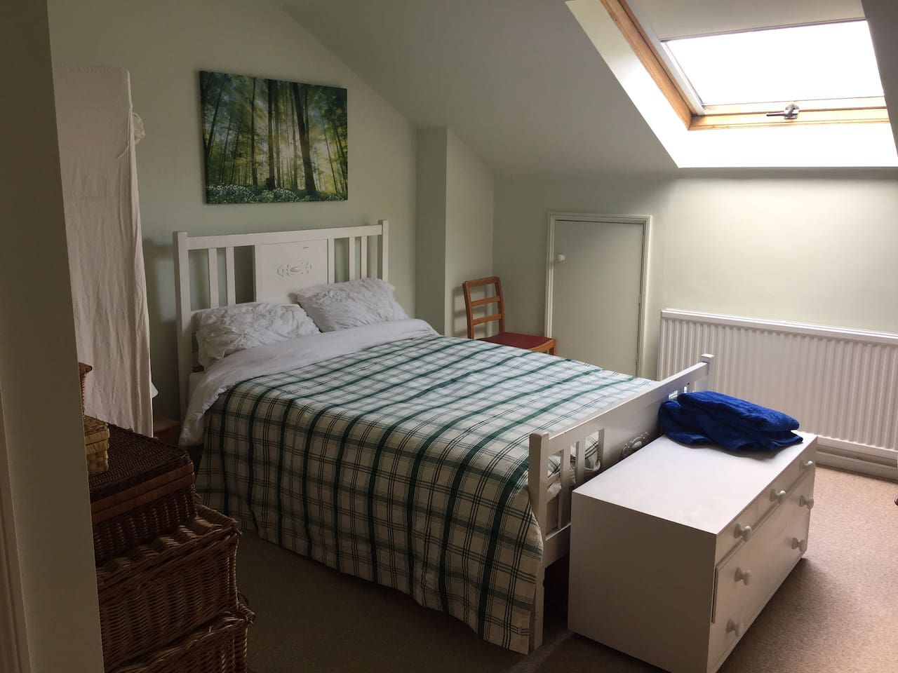 Double bed in loft room with full height ceilings and large skylight