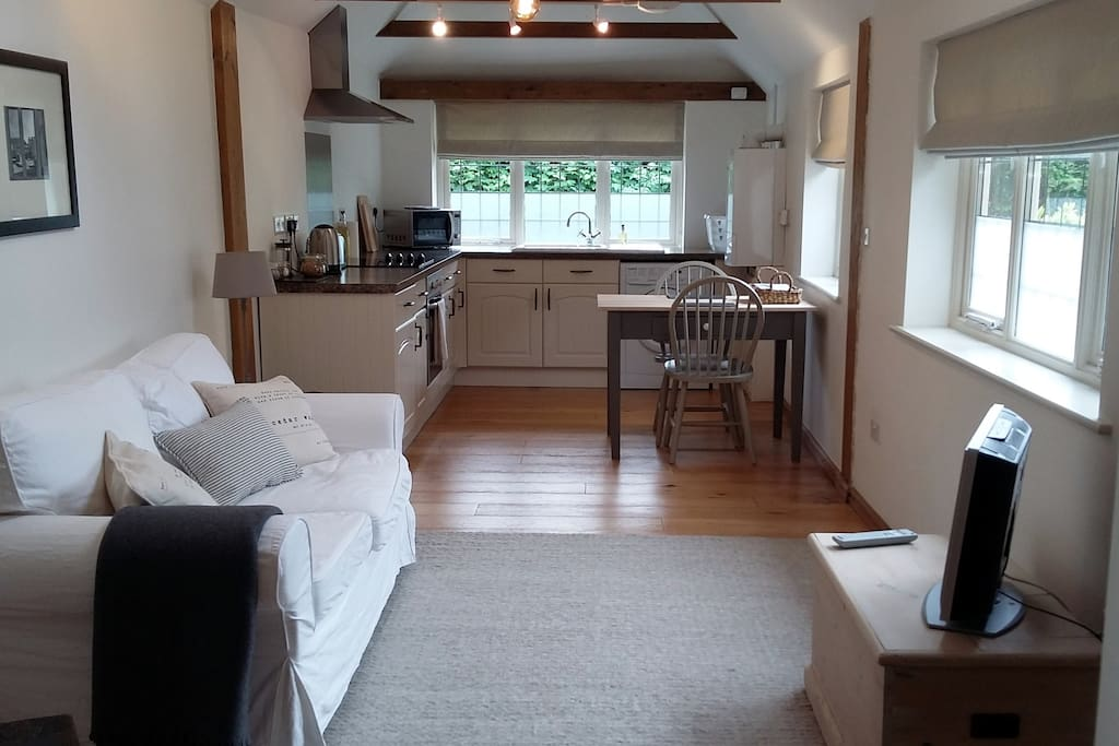 The sitting area, kitchen and dining area. The far window looks down onto the lane and hedgerow opposite.