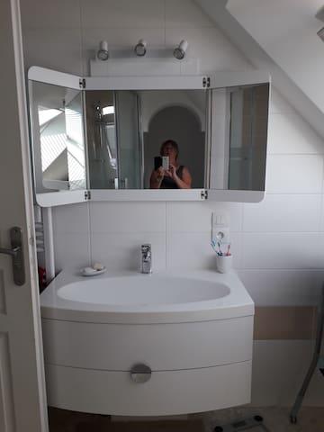 Lavabo et sèche-serviette dans une salle de bain lumineuse avec un store pour la discrétion. Depuis le vélux vous admirerez la vue à 180° sur le bocage virois. Dans cette sdb je dispose d'une baignoire et d'un matelas à langer pour bébé.