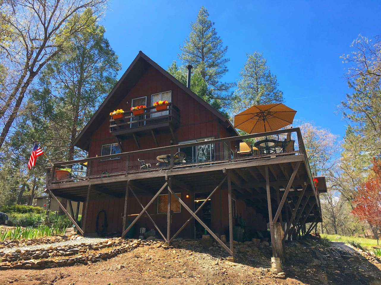 A cozy and private cabin with a huge wrap around deck, set back from the main road.