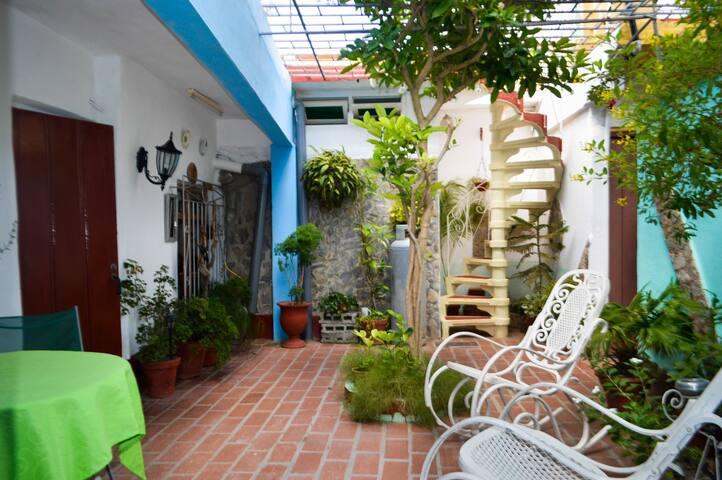Terraza con jardine delante de la habitacion con escalera da adceso a la terraza superior