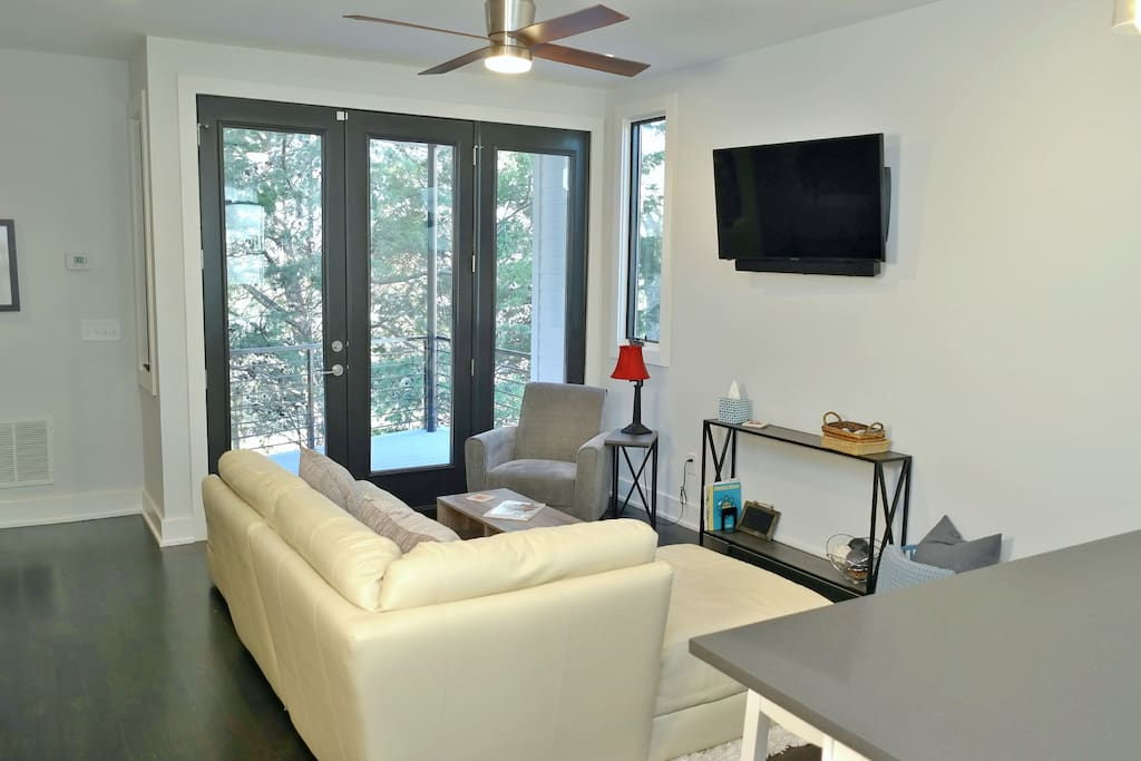 The living room is right off the kitchen and features a sectional sofa, a chair, and a TV.