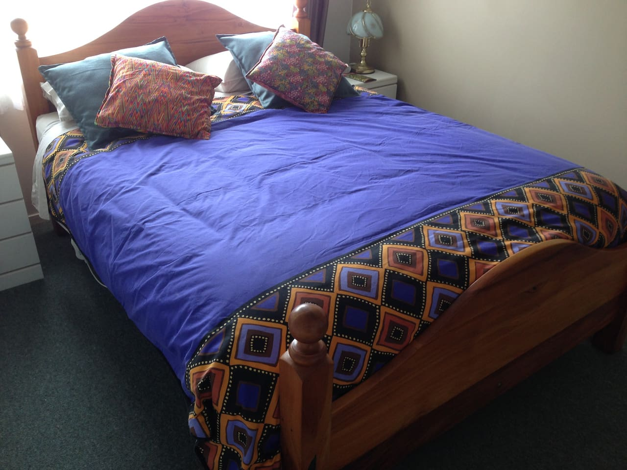 The bed  is a comfortable queen size and the room has a ceiling fan, bedside lamp,  and queen size electric blanket