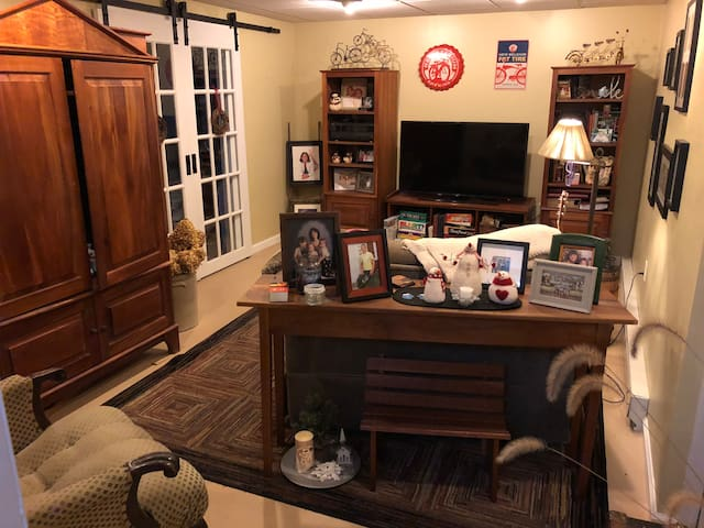 """Cozy basement TV room. Chair and a half opens into twin bed, 55"""" flat screen SmartTv with Netflix."""