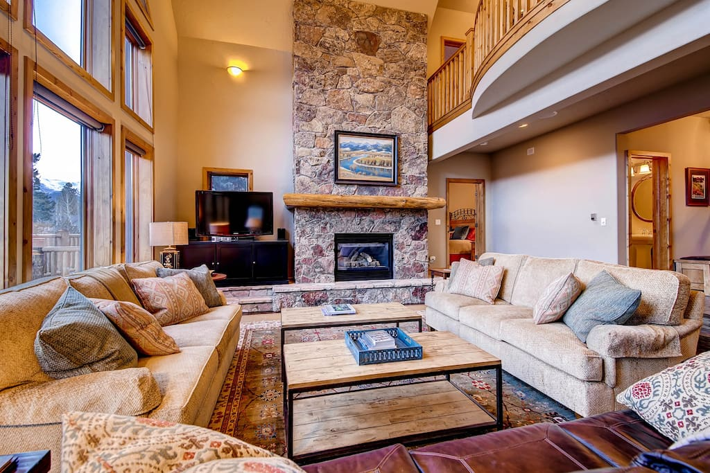Open concept living area with massive stone fireplace