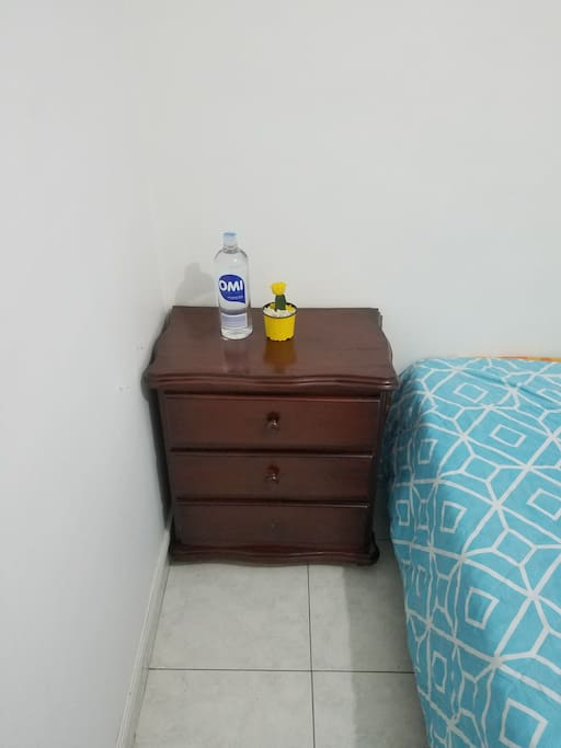 Mesa de noche con botella de agua para consumir.