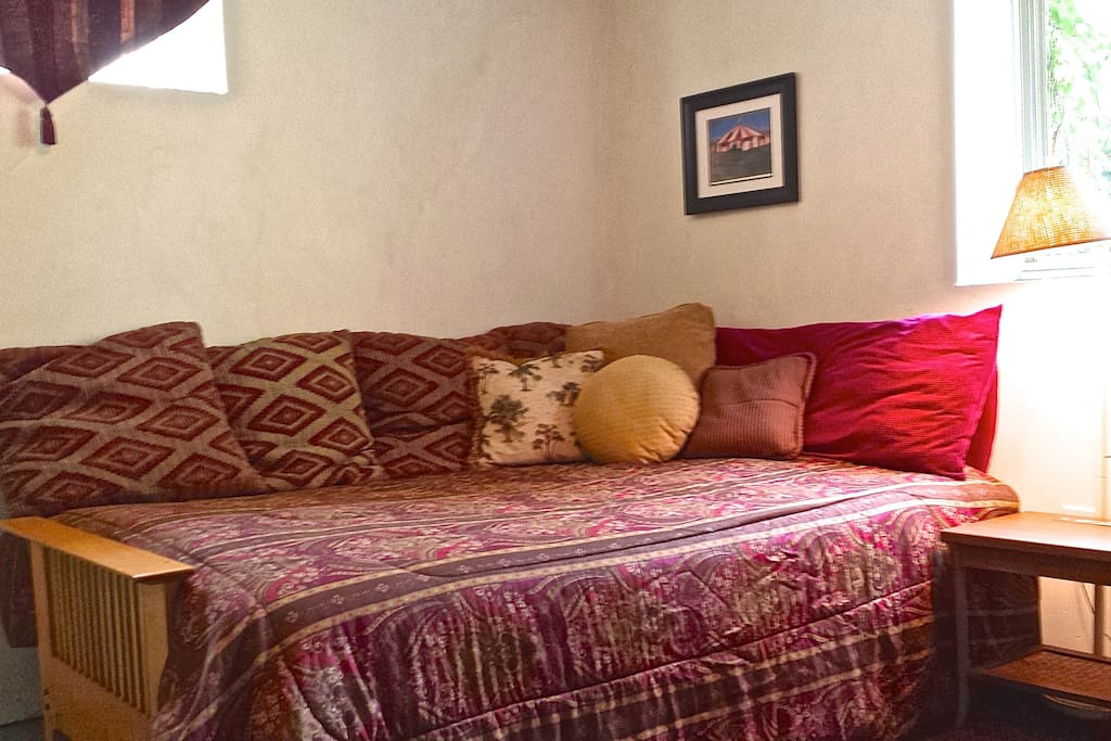 Cozy queen size bed with afternoon light. Lots of pillows for your comfort.