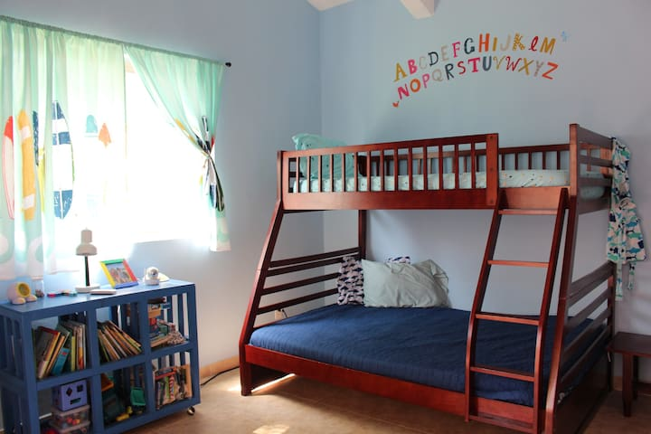 Third bedroom with bunk bed that has full on bottom and twin on top.  This room has sliding glass doors that open up to covered back patio.  It also has AC, closet and private bathroom