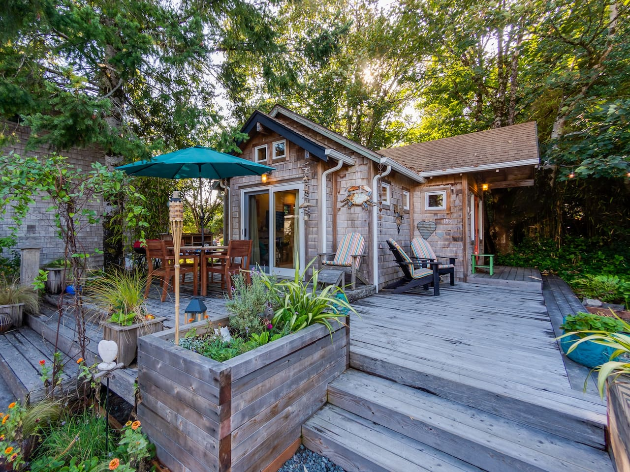 Front patio of Lil Love Shack with charcoal BBQ, table with umbrella and seating for four plus three other chairs and lounge chair, fire pit, picnic table with benches, and bench seat