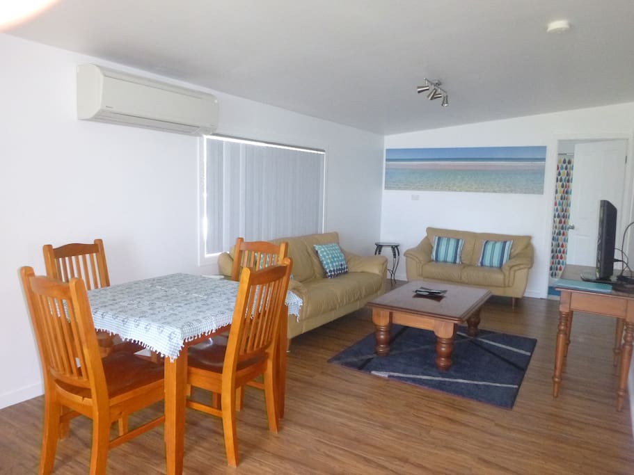 Open plan lounge, dining & kitchen with airconditioner.