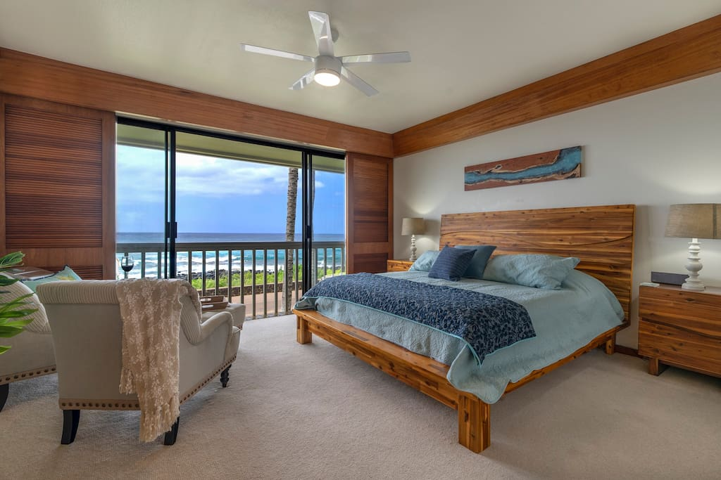 Tranquil master bedroom with doors that open to the ocean and pounding surf.