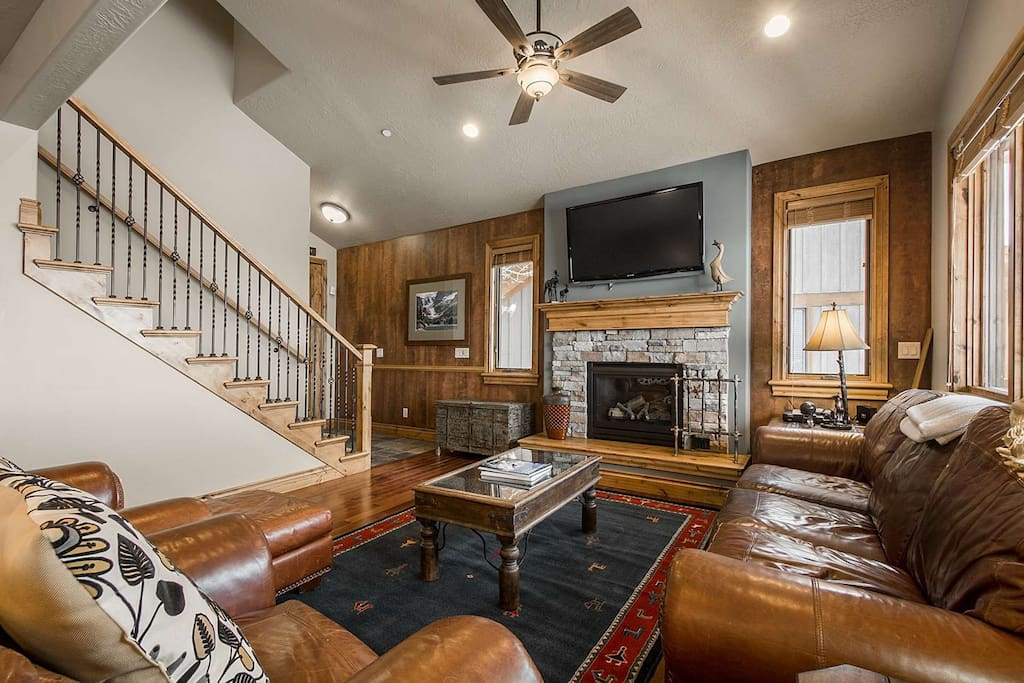 "The large formal living room features beautiful leather furniture, hardwood floors, vaulted cathedral ceilings, 50"" HDTV and gas fireplace with stone"