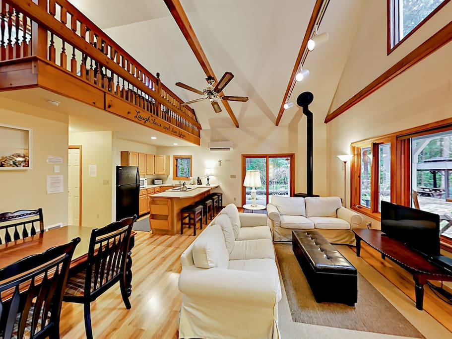 This studio cottage retreat boasts vaulted beam ceilings, a spacious loft, and wall-to-wall windows.