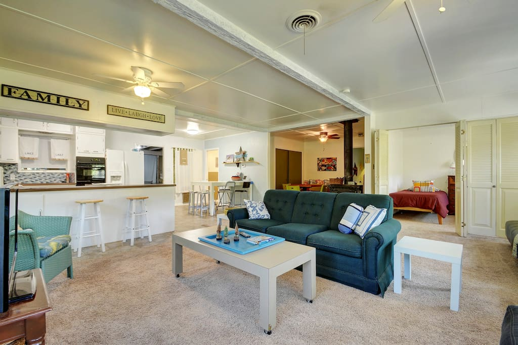 Open-concept living area with a plush carpet, a full kitchen, and comfy seating