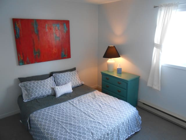 Master bedroom with new queen bed and sheet set. Custom painted dresser and abstract art.