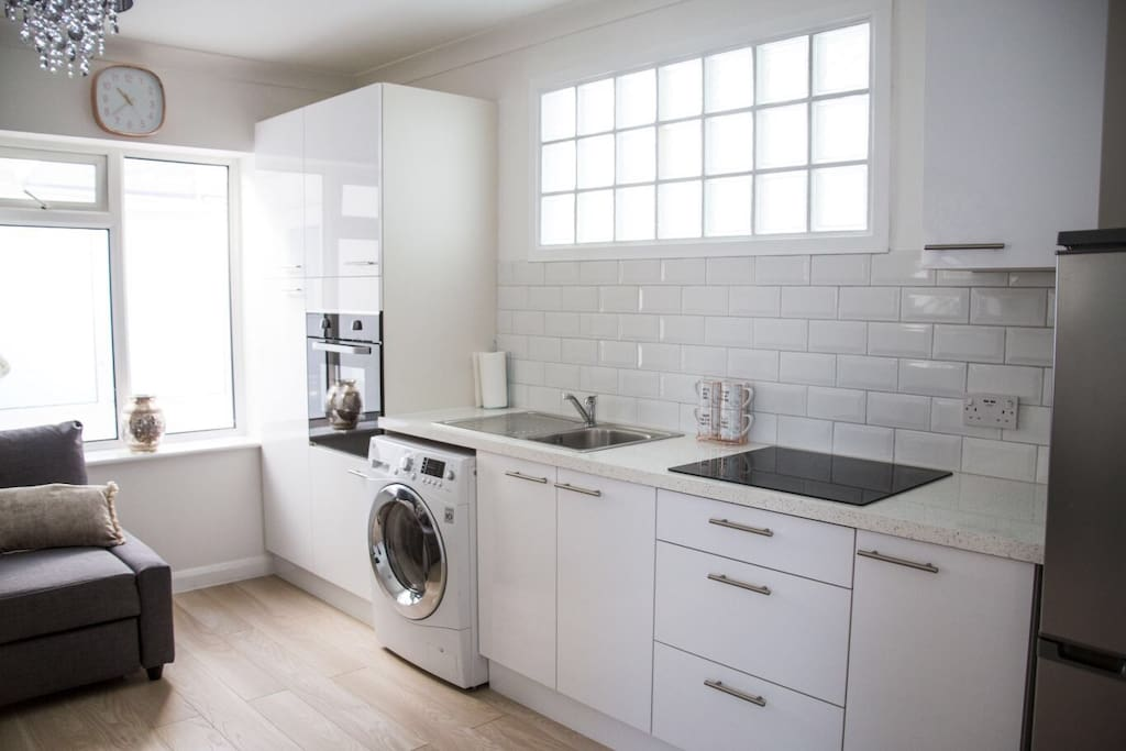 Kitchen area with washer dryer, oven, hob, fridge freezer and microwave (in cupboard).