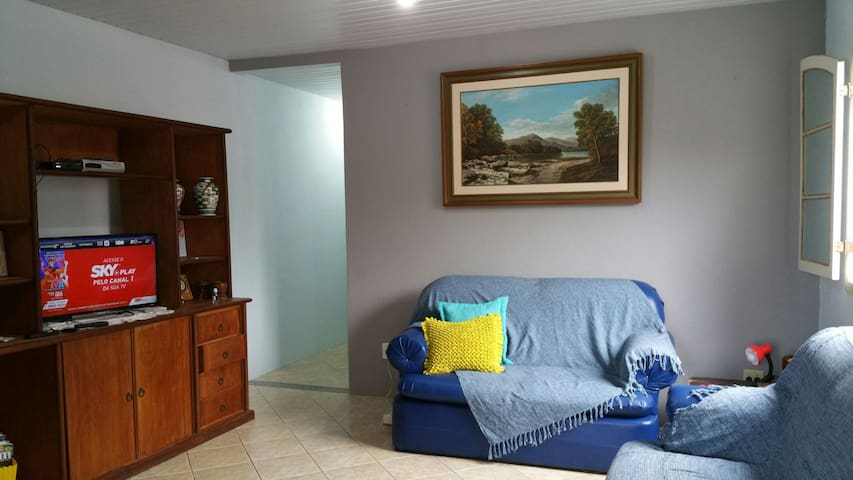 sala com dois sofás, estante, TV a cabo com pacote sky, aparelho roteador Wi-Fi.