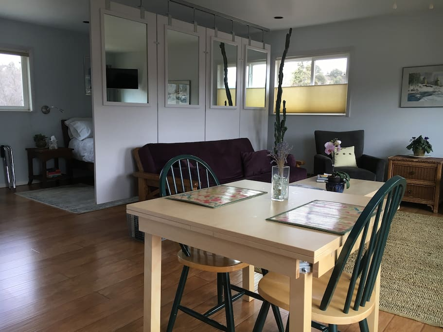 """Looking back toward the living area and bedroom from the kitchen area. Note the custom suspended room divider accent (really cool and semi-private from the bedroom). The table expands 18"""" on both ends; ample workspace for business travelers."""