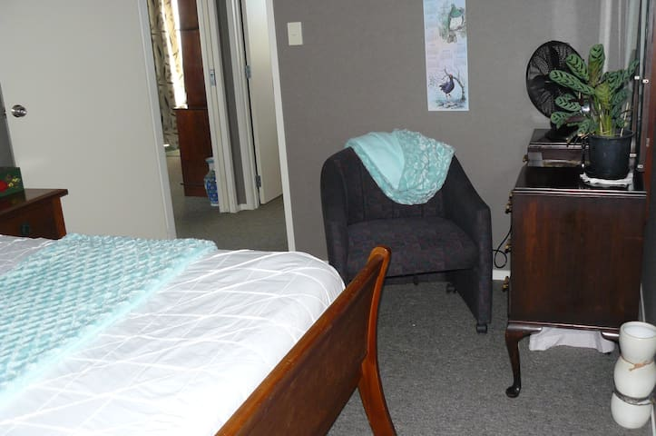 Que en size bed, dressing table, chair, bedside lamps.