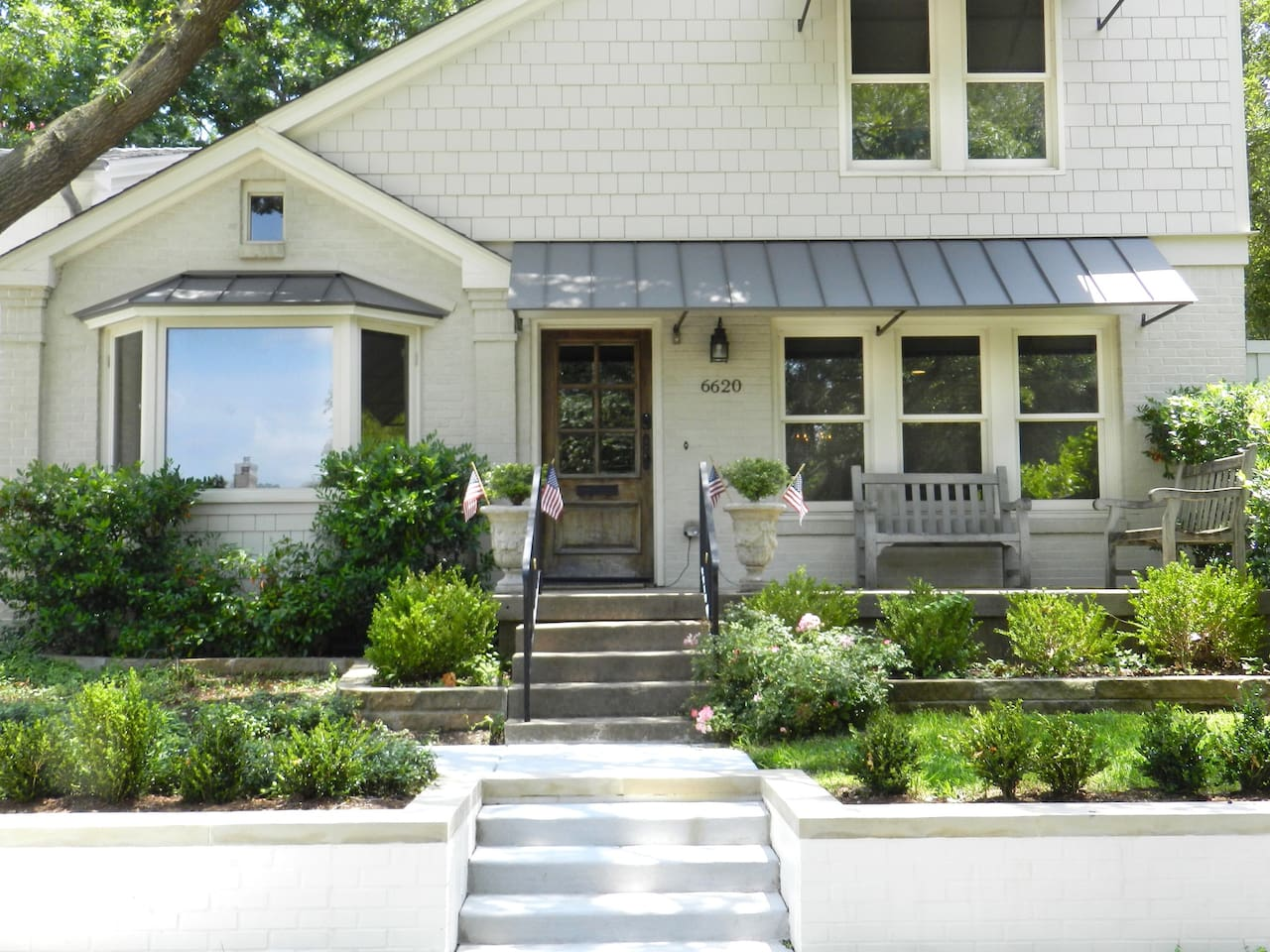 Welcome to the Cottage! Beautifully landscaped with an inviting front porch with seating.