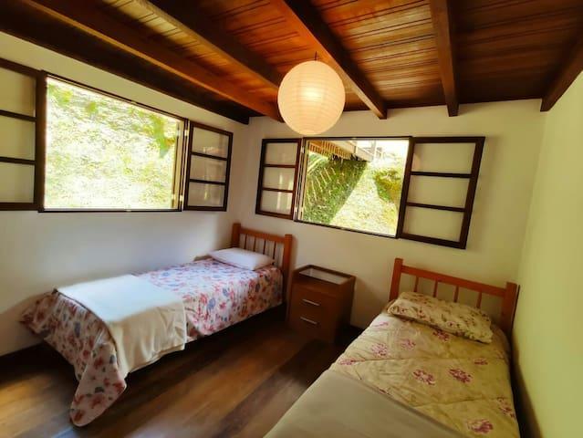 Quarto com duas camas de solteiro e uma cama auxiliar, no térreo.