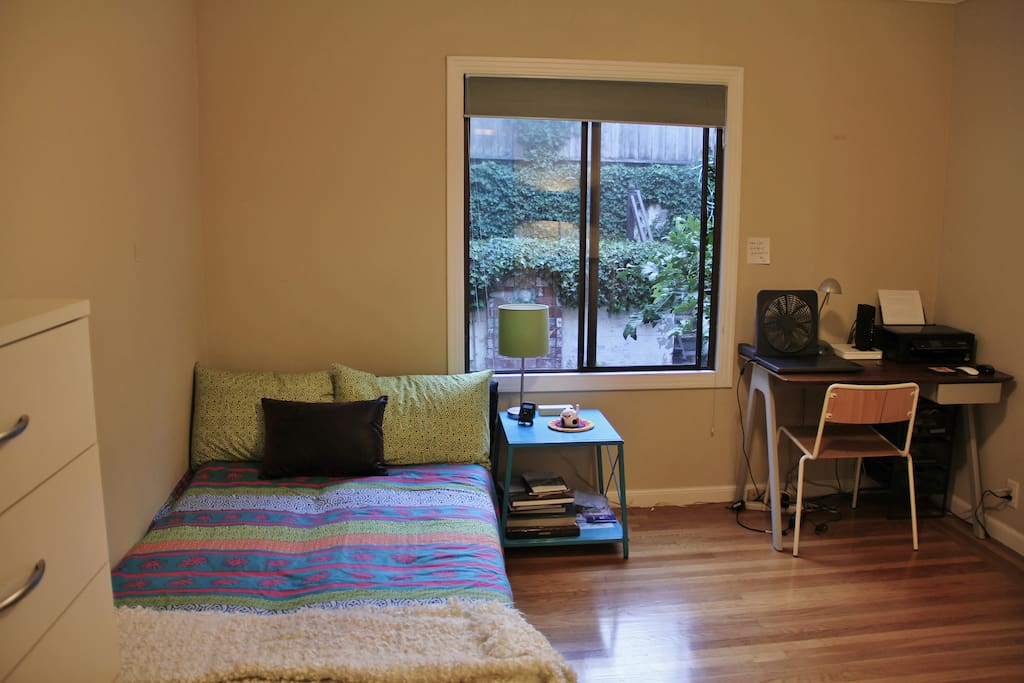The bedroom has drawers for clothes along with a desk and a big window that overlooks the garden. Open the window and enjoy the fresh air.