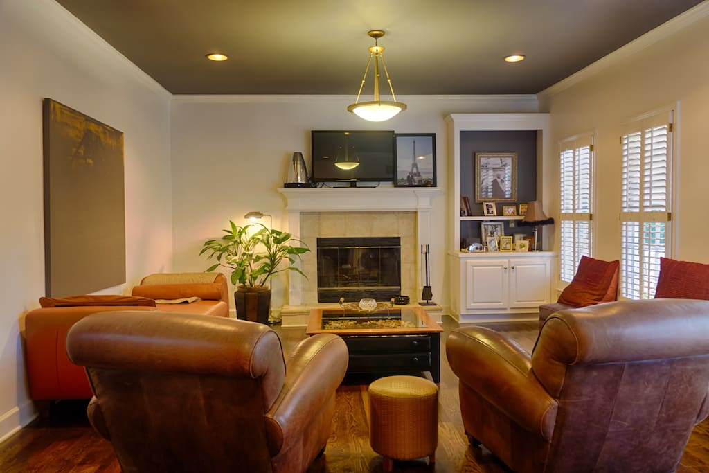 Family room with leather sofa and club chairs, wood burning fireplace and flat screen TV.