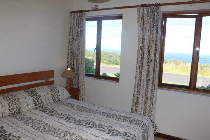 Main bedroom in cottage with double bed and sea view.