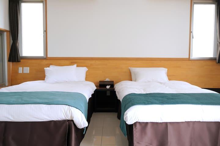 琉球ガラスヴィラのベッドルーム。シングルベッドが2台常設しています。エキストラベッドもご用意可能です。