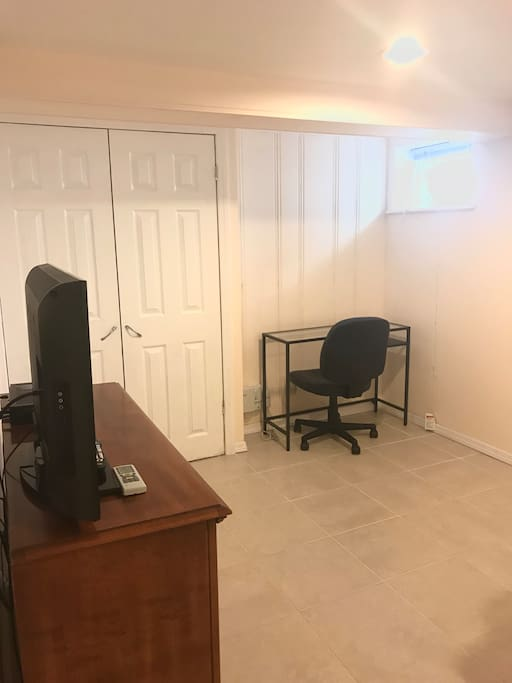 Samsung TV, closet, and 2 desks in renovated bedroom.