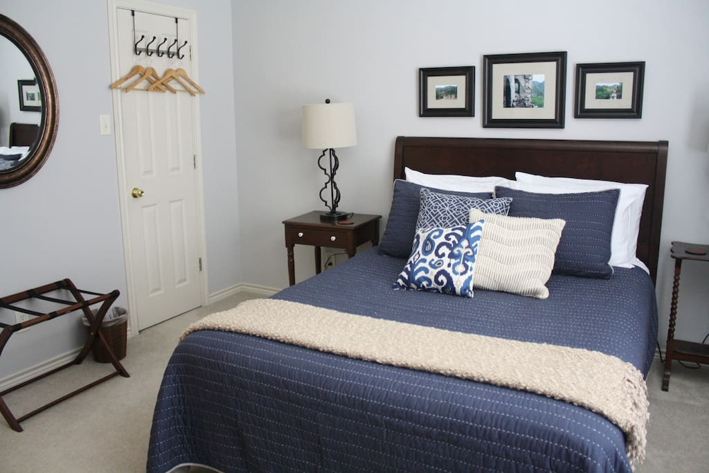 Navy room has queen bed and bathroom with walk-in shower.