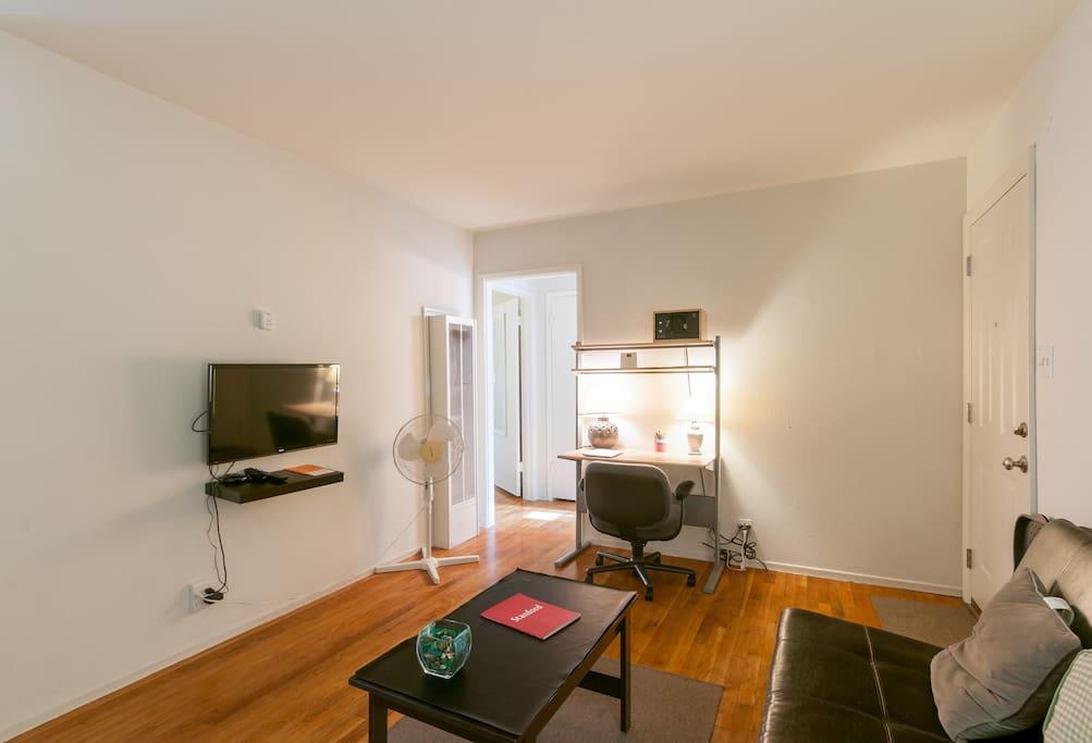 Living Room houses a leather futon, T.V. with Roku programs, 2 study desks, bookshelves, drawers and more!