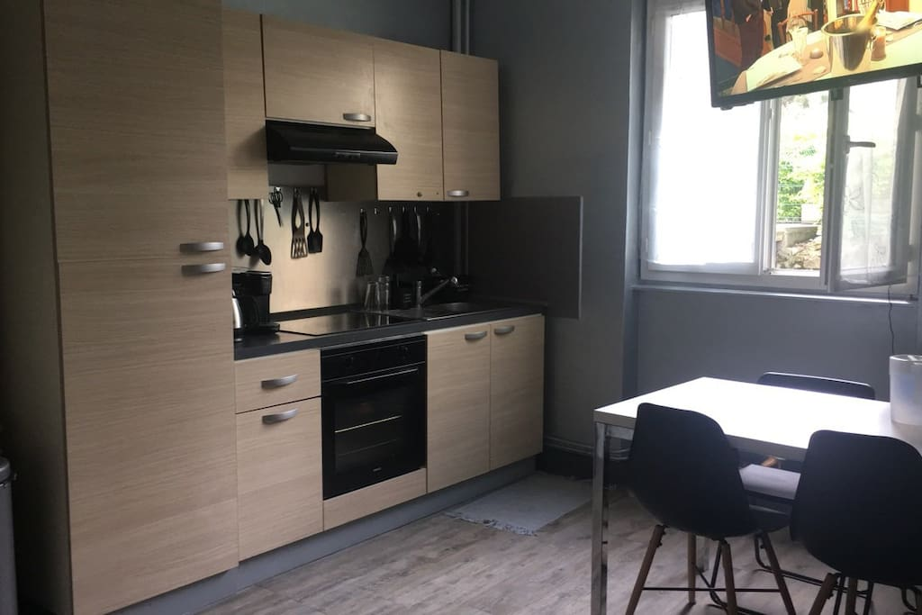 Cuisine ouverte sur le salon équipée d'un micro-onde, d'un congélateur-réfrigérateur, d'un grill-pain et d'un appareil à croque-monsieur. La fenêtre de la cuisine donne sur la cour.