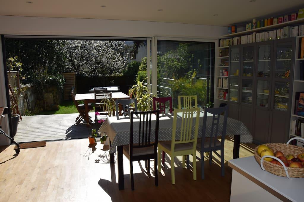 Salle à manger avec baie vitrée 3 vantaux donnant sur terrasse