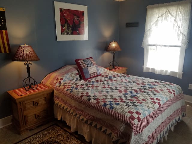 Bedroom 2 Queen Bed Comfortable room with designer bedding, folk art, handmade furniture, and hand wrought lighting.