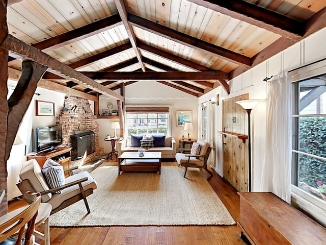 Cozy living area with vaulted ceilings, wood beams, and original stone fireplace.