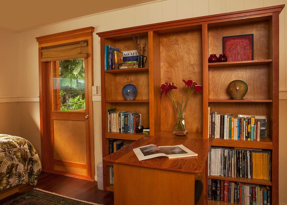 Opposite end of master bedroom, showing bottom of twin daybed, door to back lanai, and desk/shelves.