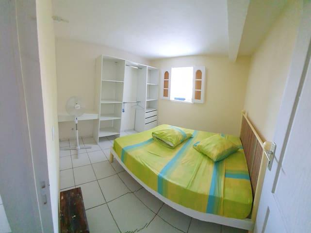 Deuxième chambre équipée d'un lit double, d'une pendrie et d'un ventilateur.