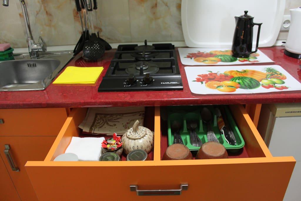 в ней газовая мини-плита с двумя конфорками, газовая колонка, вытяжка, раковина, холодильник, комплект посуды
