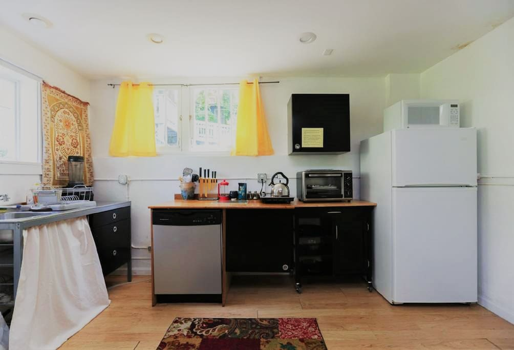 Kitchen with refrigerator, microwave, oven, cooktop, dishwasher, sink, water filter, coffee maker, French press, vitamix, cookware, utensils, and all dishes/glasses
